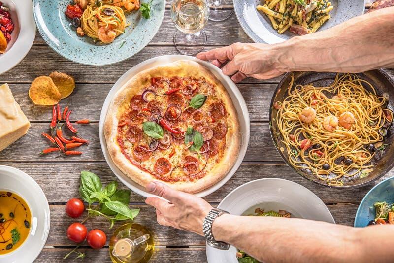 Salame da pizza nas mãos do cozinheiro Cozinheiro chefe que serve o diavolo da pizza na tabela média completamente de refeições i imagem de stock