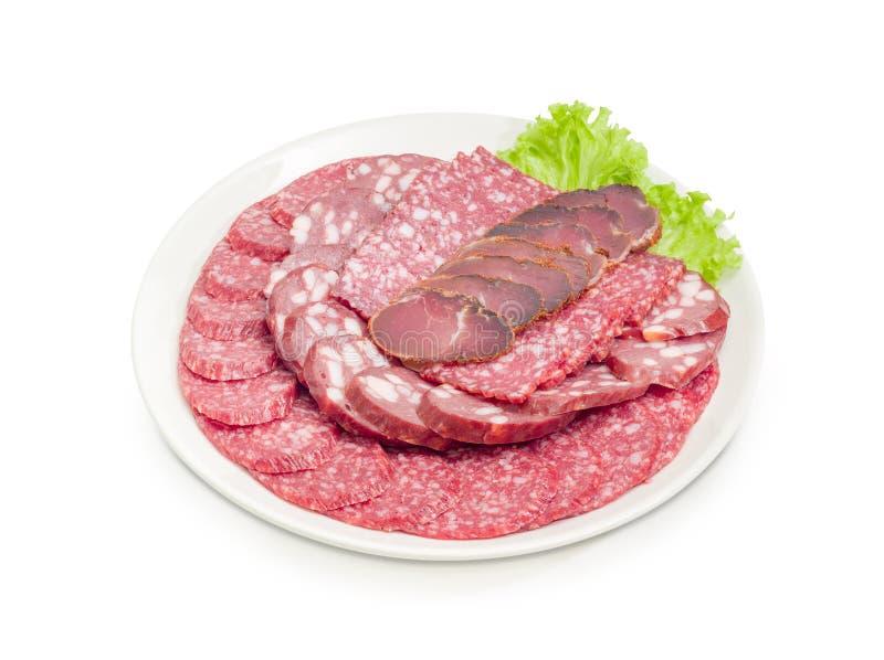 Salame diferente cortado e outros produtos de carne no prato branco fotografia de stock royalty free