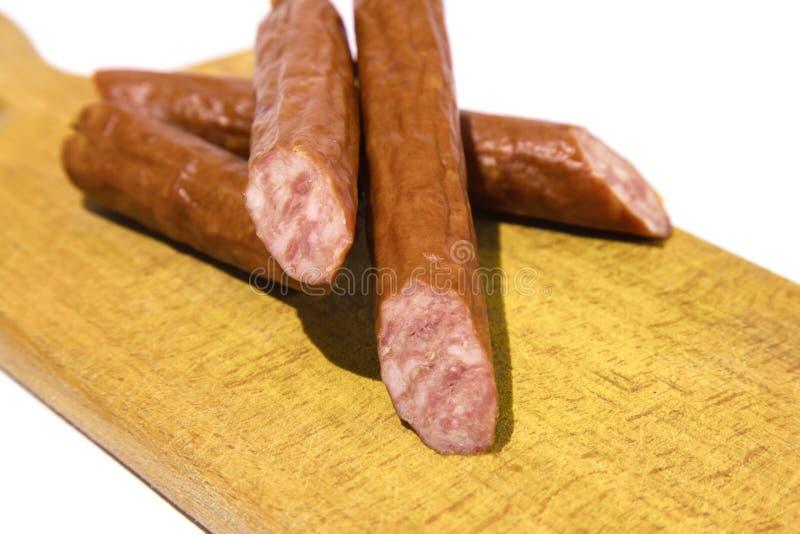 Salame fresco em um trencher de madeira em um fundo branco fotografia de stock