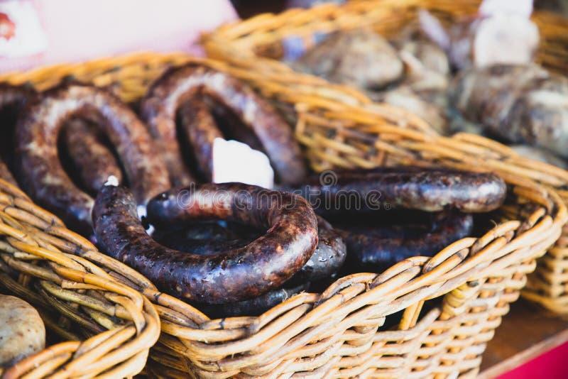 Salame o salsiccia asciutto della carne sul canestro di vimini immagini stock