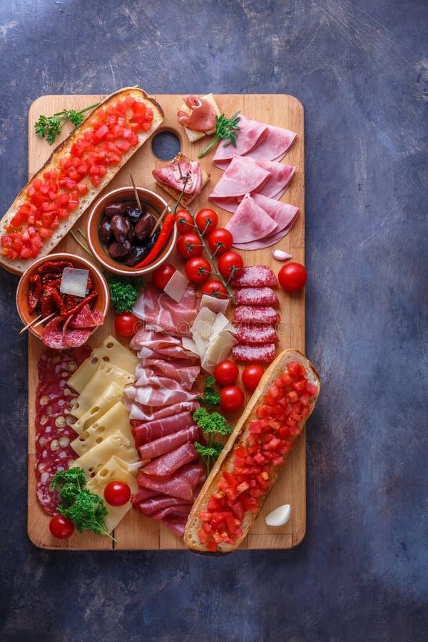 Salame, presunto cortado, salsicha, prosciutto, queijo, tomate Placa do antipasto da carne na tabela de pedra Vista superior com  fotografia de stock royalty free
