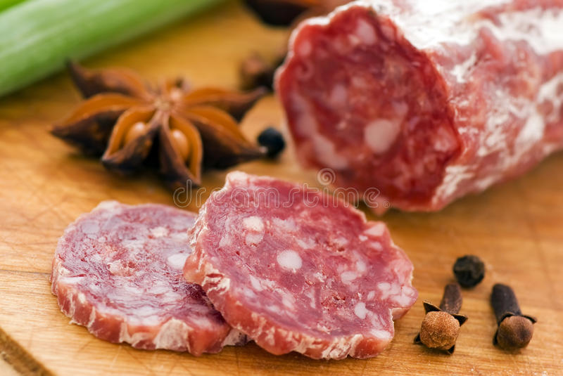 Salami. Red salami with herbs as closeup on a wood plate royalty free stock image