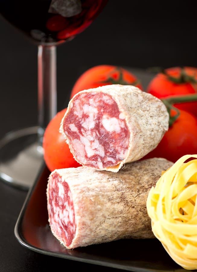 Salami auf Platte mit Tomatenteigwaren und Rotwein lizenzfreies stockfoto