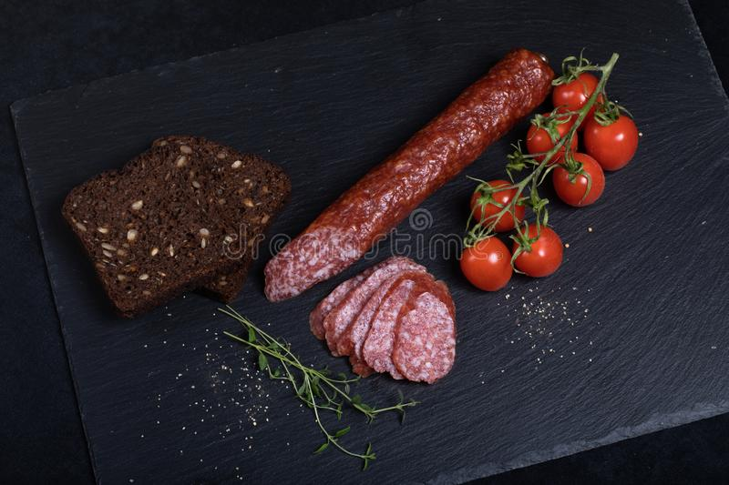 Salami on black stone plate. With bread and cherry tomatoes royalty free stock image