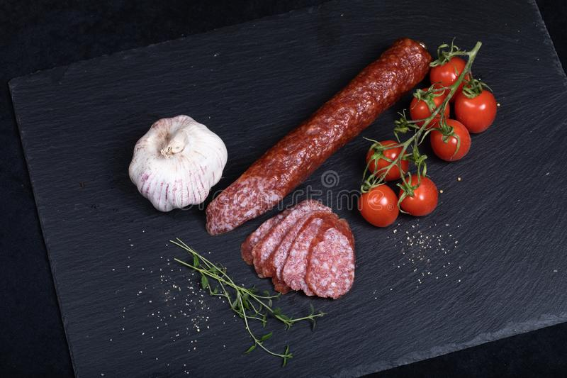 Salami on black stone plate. Close up of smocked sausage with garlic and cherry tomatoes royalty free stock images
