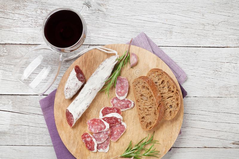 Salami, bread and wine. Salami, bread and red wine glass. Meat antipasto platter on wooden table. Top view stock photo