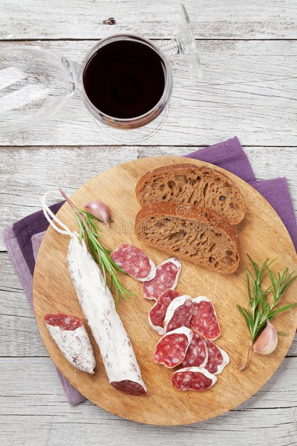 Salami, bread and wine. Salami, bread and red wine glass. Meat antipasto platter on wooden table. Top view royalty free stock images