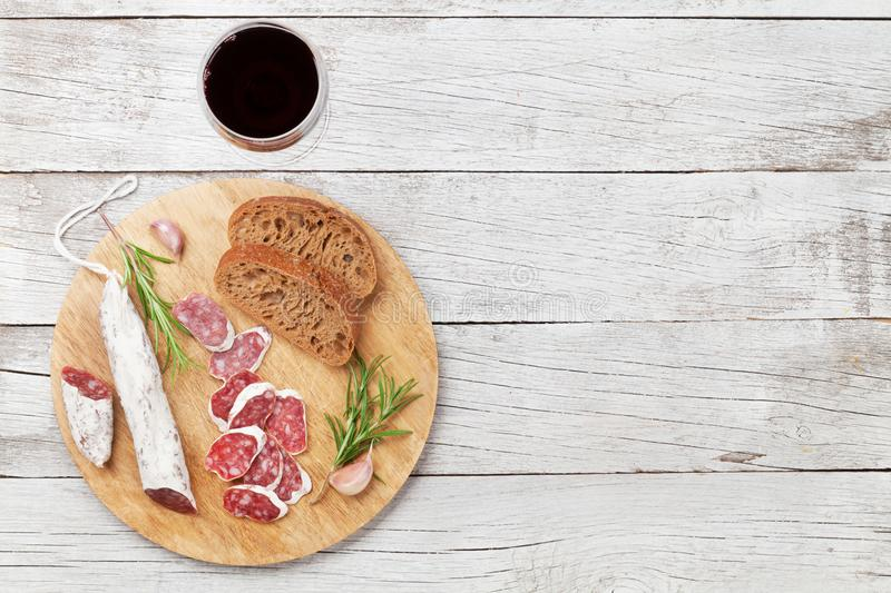 Salami, bread and wine. Salami, bread and red wine glass. Meat antipasto platter on wooden table. Top view with copy space stock photo