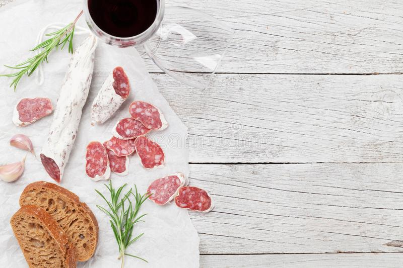 Salami, bread and wine. Salami, bread and red wine glass. Meat antipasto platter on wooden table. Top view with copy space royalty free stock photos