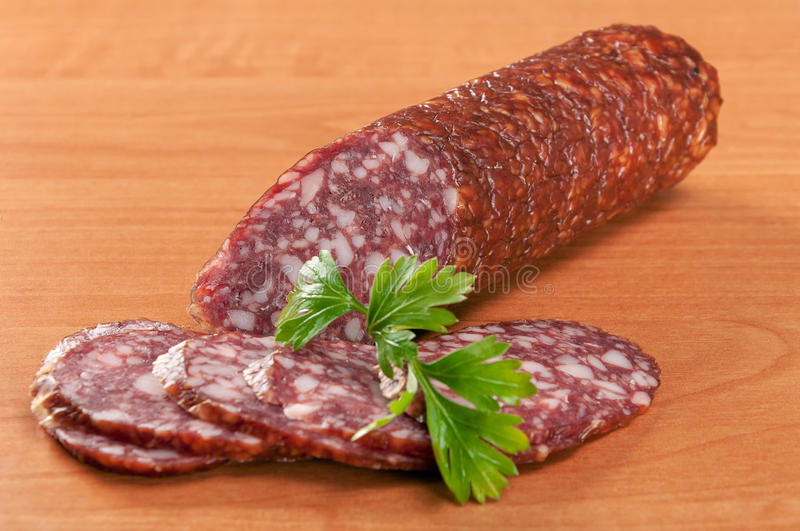 Salami for Breakfast with pepper on a wooden table royalty free stock image