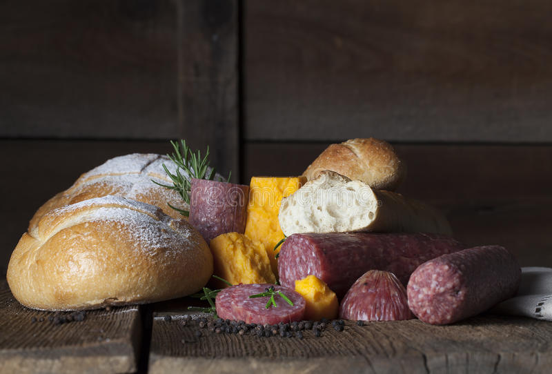Salami Cheese Bread Loaves. A sliced salami topped with sprig of fresh rosemary and black peppercorns, salami, round and baguette loaves of bread and sharp stock images