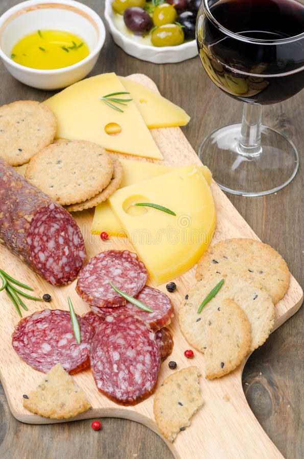Salami, cheese, crackers, olives and a glass of wine. On a cutting board vertical royalty free stock photography