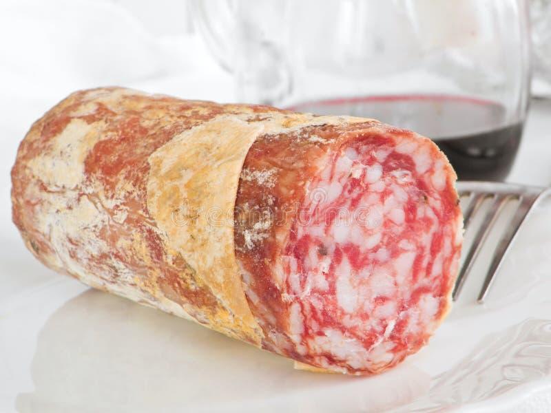 Salami com a forquilha no prato branco. fotos de stock