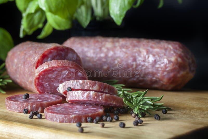 Salami coupé en tranches sur le conseil en bois photo libre de droits
