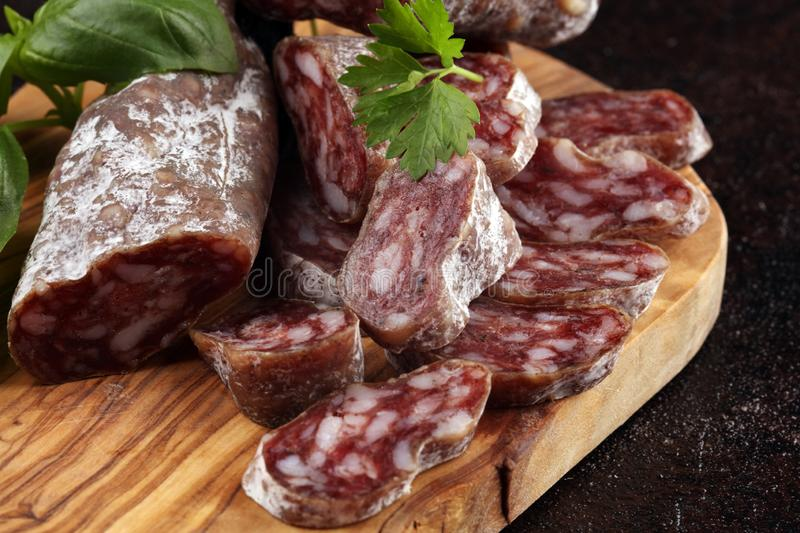 Salami cut. thinly sliced salami on a wooden texture on the background stock photo