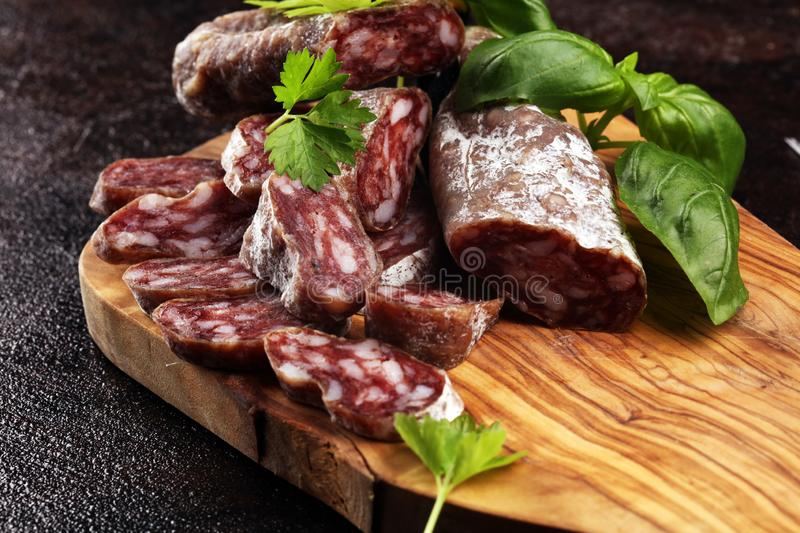 Salami cut. thinly sliced salami on a wooden texture on the background royalty free stock image