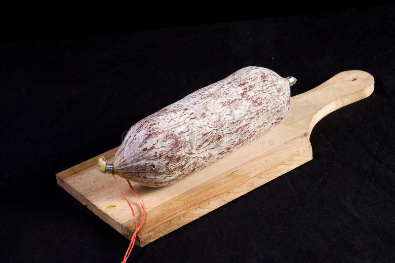 Salami on cutting board. Dried salami roll on wooden cutting board against black background royalty free stock photos