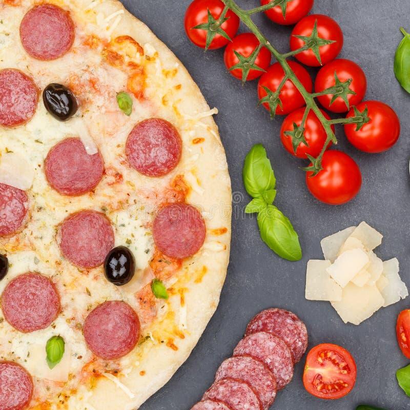 Salami de los salchichones de la pizza desde arriba de los ingredientes que cuecen cuadrados cercanos encima de pizarra fotos de archivo libres de regalías