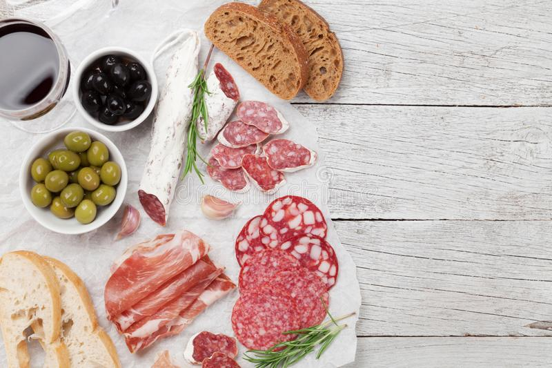 Salami, ham, sausage, prosciutto and wine. Salami, sliced ham, sausage, prosciutto, bacon, toasts, olives. Meat antipasto platter and red wine on wooden table royalty free stock photo