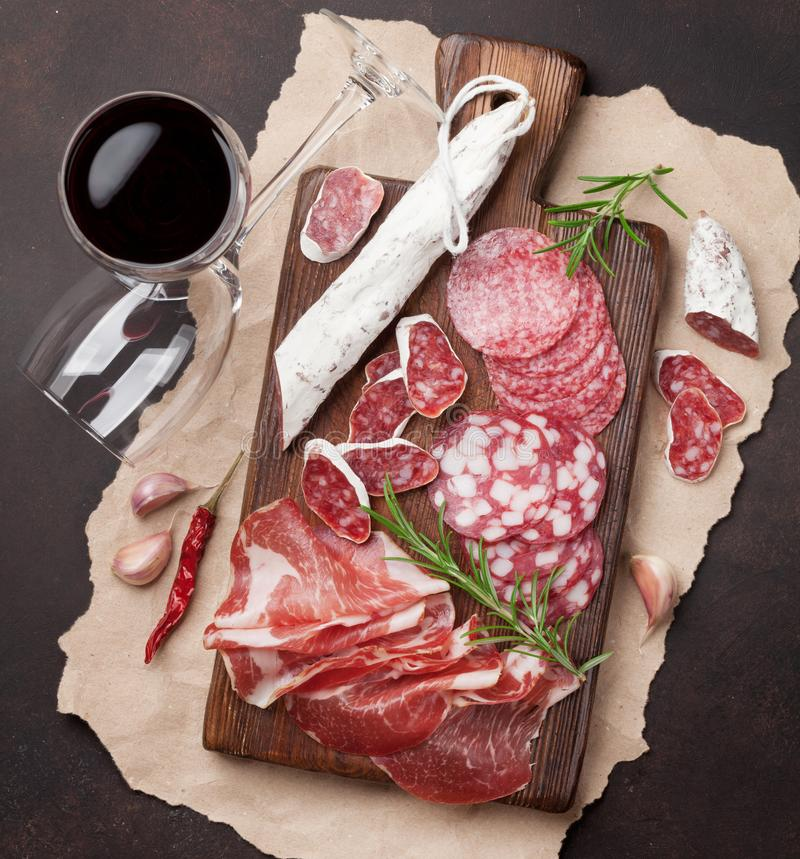 Salami, ham, sausage, prosciutto and wine. Salami, sliced ham, sausage, prosciutto, bacon. Meat antipasto platter and red wine on stone table. Top view stock photos
