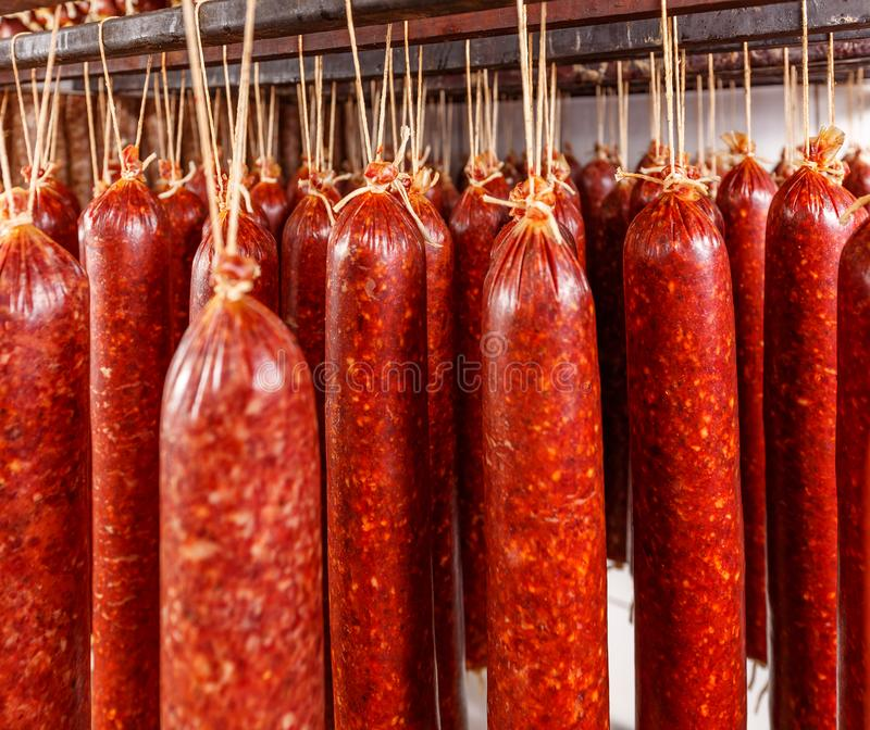 Salami hanging on a rope. On a metal frame in the smoke house stock photography