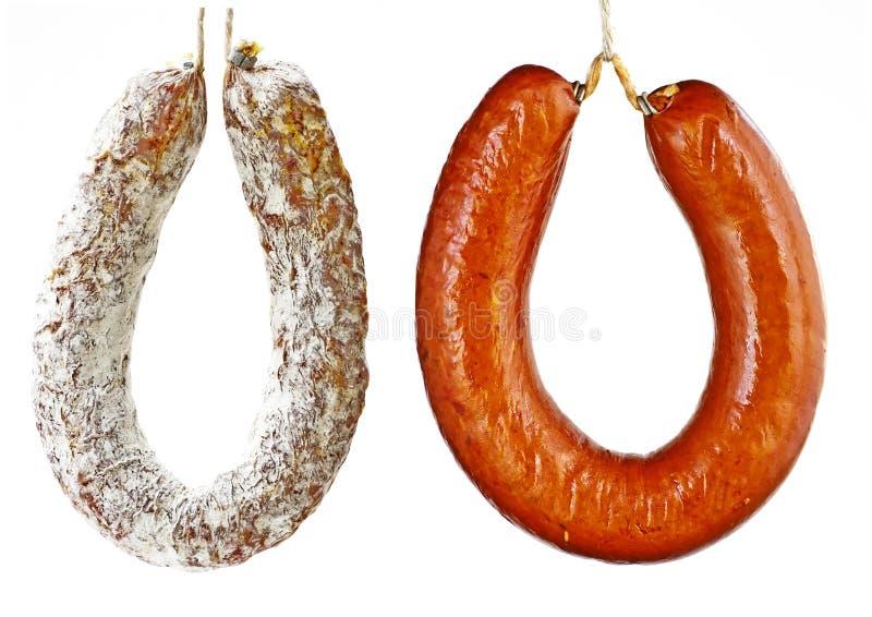 Salami and kolbash sausage. A pair of hanging round sausages royalty free stock photos