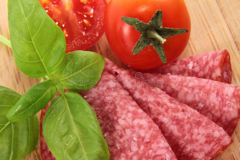 Salami mit Tomate und Basilikum lizenzfreie stockfotografie