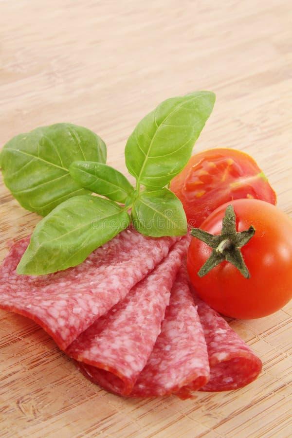 Salami mit Tomate und Basilikum lizenzfreies stockbild
