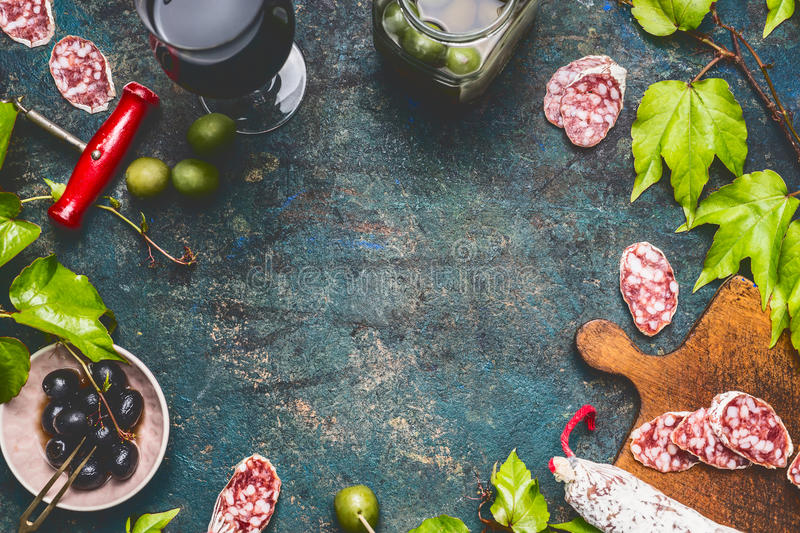 Salami,olives, glass of red wine, grape leaves and cork opener . Italian style on dark rustic vintage background, top view royalty free stock photos