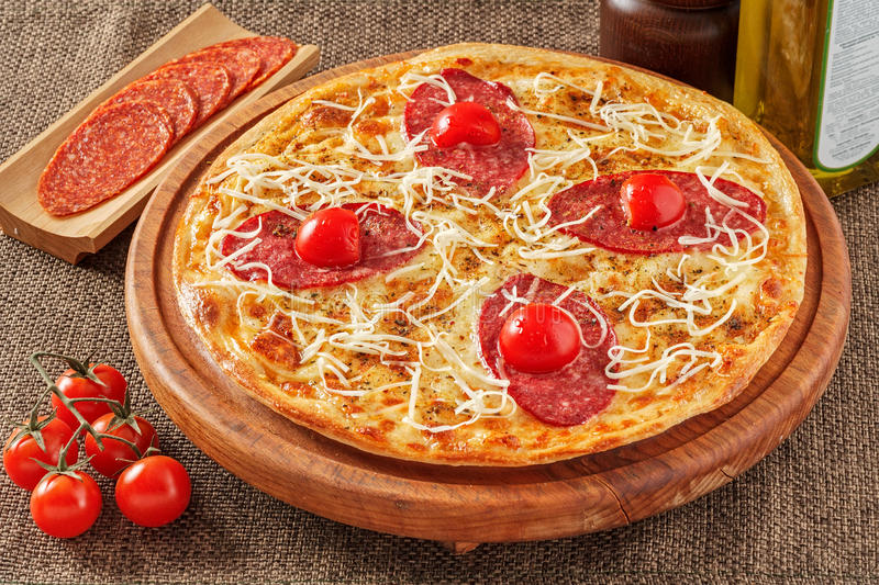 Salami pizza with cherry tomatoes stock images