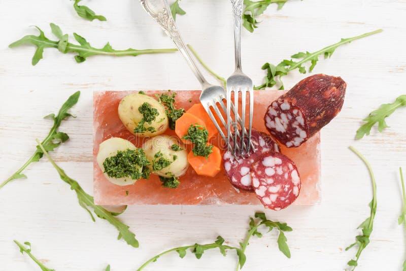 Salami, potatisar, morötter och ny arugula med grön chimichur arkivbilder