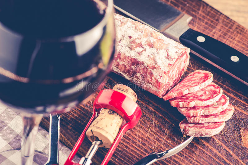 Salami and red wine. Italian food concept royalty free stock image
