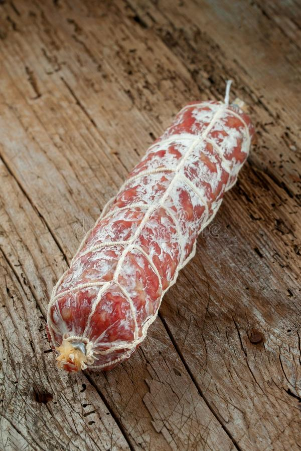 Salami sausages sliced with pepper, garlic and rosemary on cutting board on wooden table. stock photos