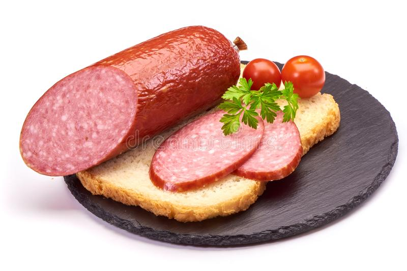 Salami sausages sliced with pepper, garlic and rosemary on cutting board on wooden table. stock photo