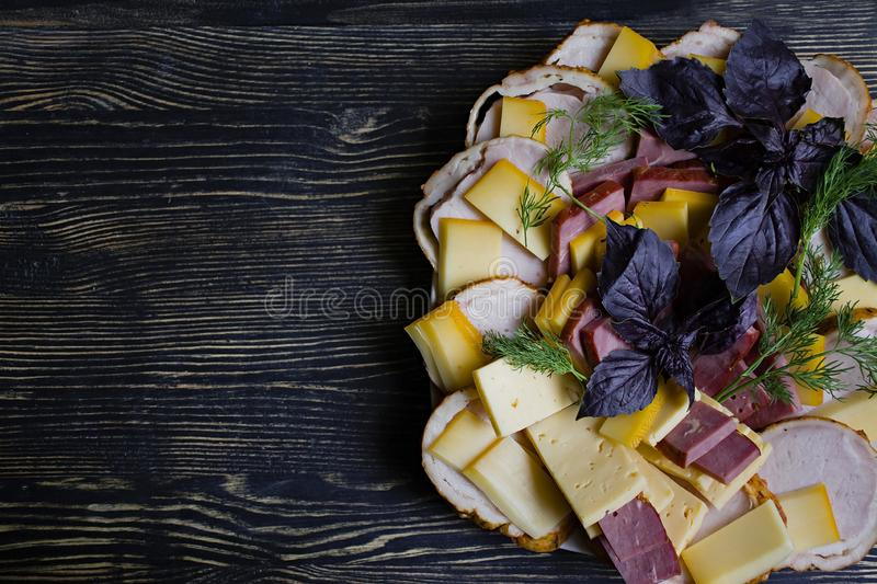 Salami, sliced ham and cheese salad and vegetables. Squeezing sausage and cured meat on a festive table stock images