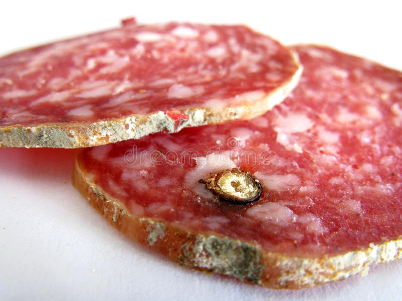 Salami slices. Closeup of two salami slices with pepper grain royalty free stock photography