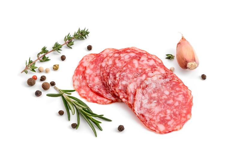 Salami slices with black pepper. Rosemary and garlic on white background. Cured sausage and spices royalty free stock photo