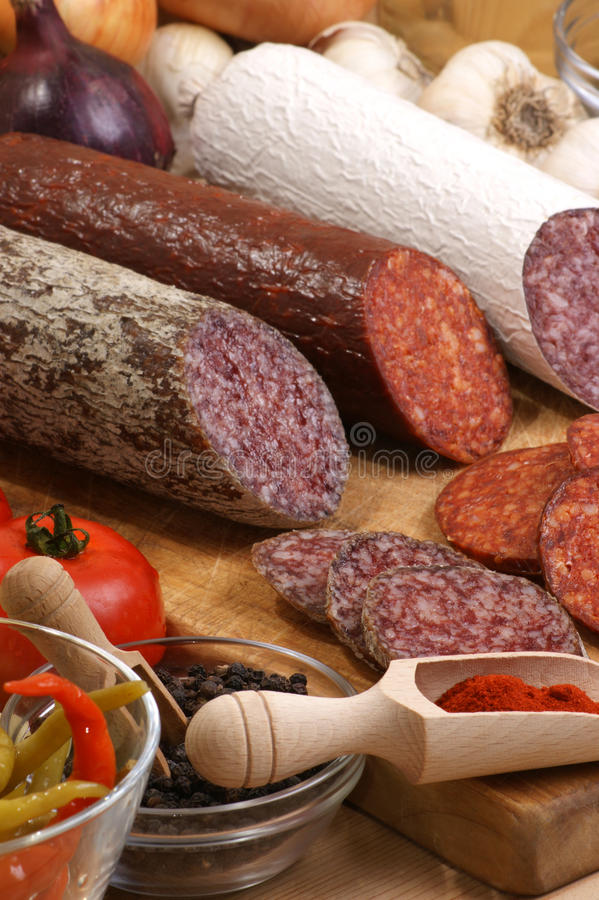 Salami and slices salami on a timber board royalty free stock photography