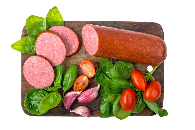 Salami smoked sausage with basil, garlic and tomatoes on wooden cutting board isolated on white background royalty free stock images
