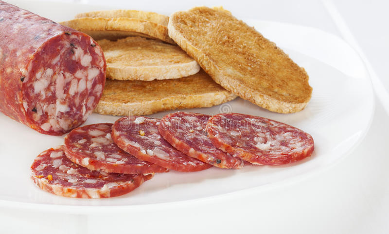 Salami and Toast on Plate. Salami on a white plate with toast. This is the ordinary, vacuum packed, supermarket salami stock photos