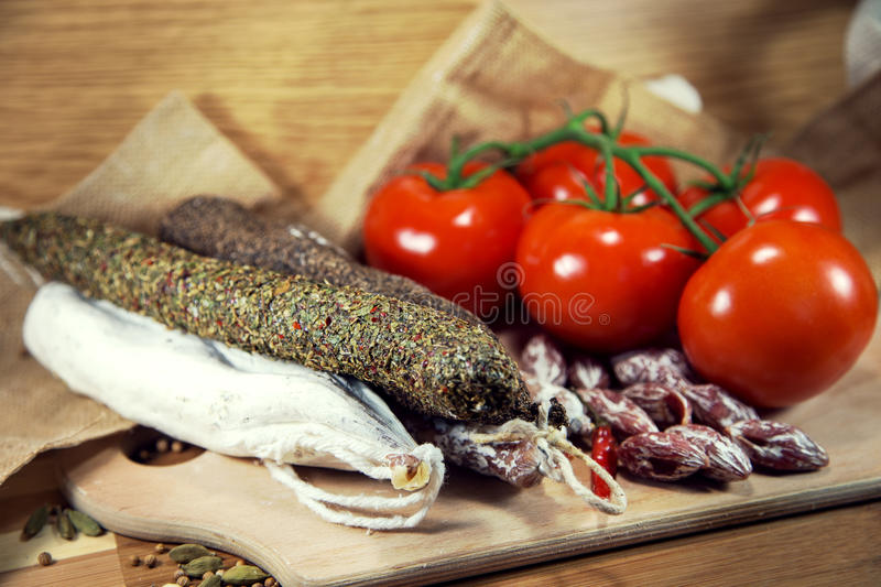 Salami with tomatoes on wood royalty free stock images