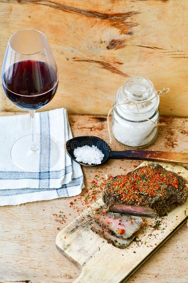 Salami and wine. Different kinds of Salami ,cold cuts,, empty glass for red wine peperoncino, fresh onion and spices as a rustic lunch stock image