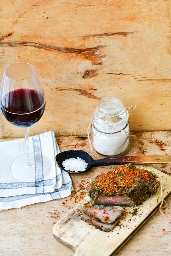 Salami and wine. Different kinds of Salami ,cold cuts,, empty glass for red wine peperoncino, fresh onion and spices as a rustic lunch royalty free stock image