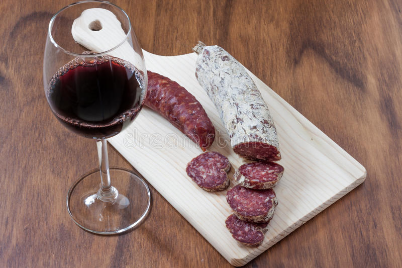 Salami and wine. One sliced salami and a sausage on a wood cutting board and a red wine glass on a wooden table. The slices are heart shaped stock photography
