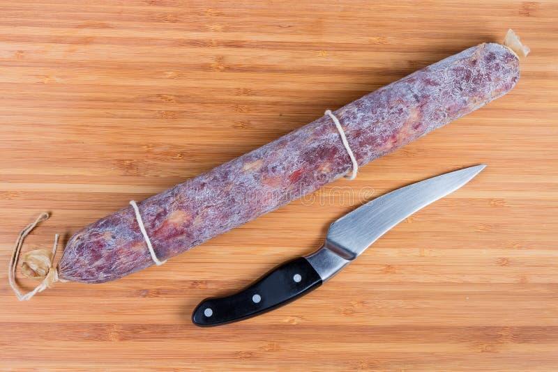 Salami y cuchillo de cocina enteros en la tabla de cortar de madera fotografía de archivo