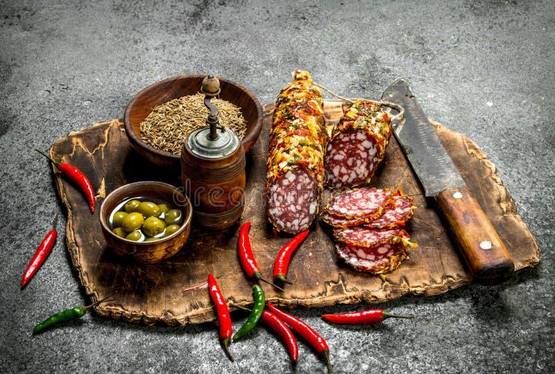 Salami z pikantność i gorącymi pieprzami na desce zdjęcia stock