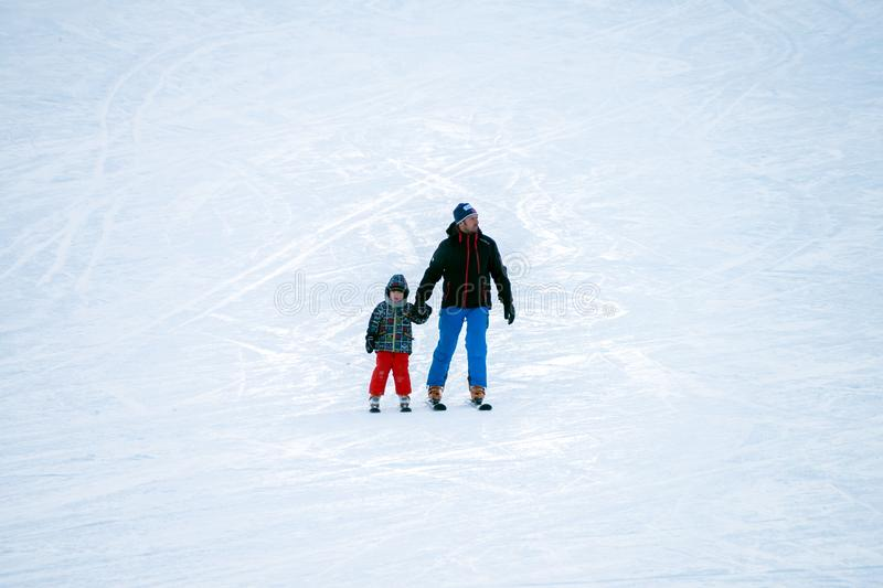 Father with son go skiing from the side of the mountain royalty free stock images