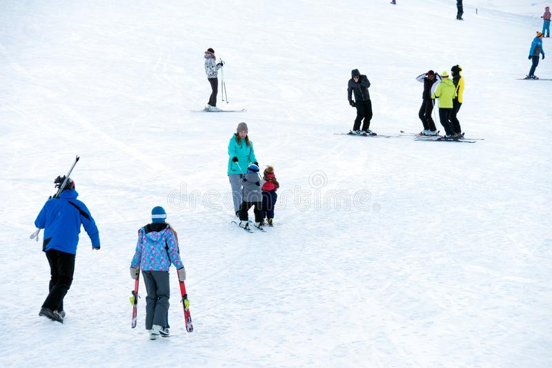 Real people skiing on the mountainside at the weekend stock image