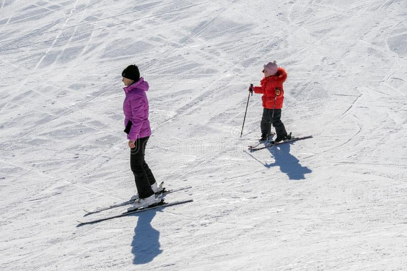 Mom and daughter go skiing from the side of the mountain stock photo