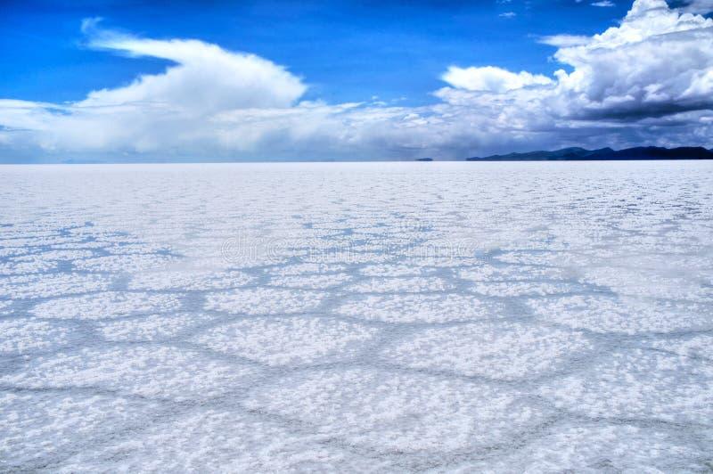 Salar de Uyuni Bolivia salt desert and cloudy blue sky. Salar de Uyuni Bolivia - panorama of the perfect white flat salt desert with blue cloudy sky. Visible stock image
